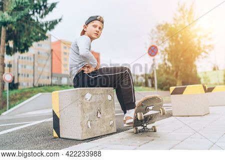Teenager Skateboarder Boy Portrait In A Baseball Cap With Old Skateboard On The City Street. Youth G