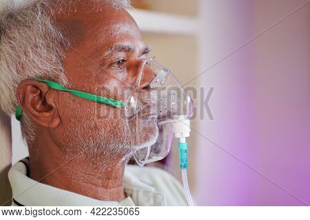 Close Up Head Shot Of Old Man Breathing On Ventilator Oxygen Mask At Home Due To Coronavirus Covid-1
