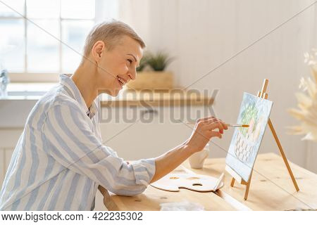 Creative Hobby, Digital Detox. Side View Of Smiling Mature Woman Painting Picture At Home While Sitt
