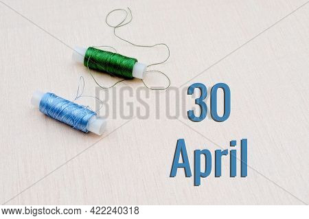 Handicraft Calendar 30 April. Skeins Of Green And Blue Threads For Embroidery On A Beige Background.