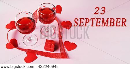 Calendar Date On Light Background With Two Glasses Of Red Wine, Red Gift Box And Red Hearts With Cop