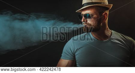 Bearded Brutal Male In Hat And Sunglasses Smoking A Vapor Cigarette As An Alternative To Tobacco. St