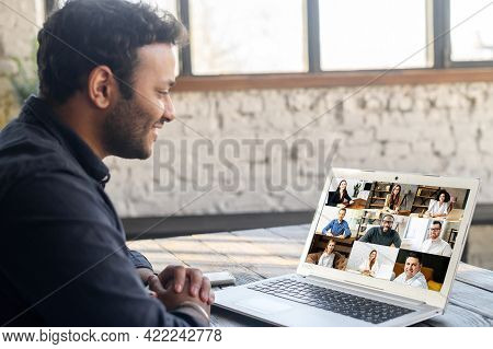 Morning Meeting On The Distance. Back View Over Shoulder Of Hindu Guy To The Laptop Screen With A Lo