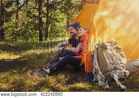 Camping Trip - Young Couple Sitting In Tent At Campsite And Relaxing After Hike