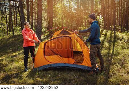 Young Couple Set Up A Tent Together In Forest. Outdoor Adventure, Camping Trip