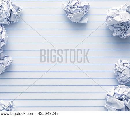 School supplies of blank lined notebook paper surrounded by more trashed balled up paper. Studying or writing mistakes concept.