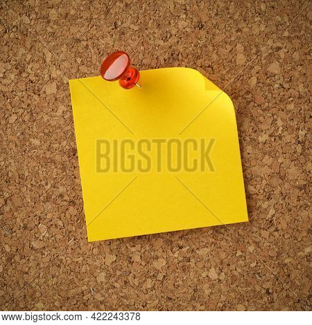 Blank yellow sticky note pinned with red tack. Empty copy space for important office notice, message, or reminder.