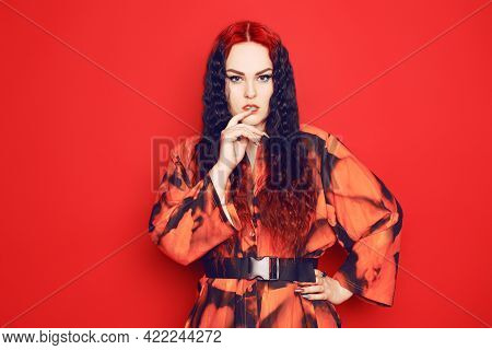 Beautiful Girl On A Red Background. Brunette With Red Roots Of Curled Hair In A Red Dress And Red Li