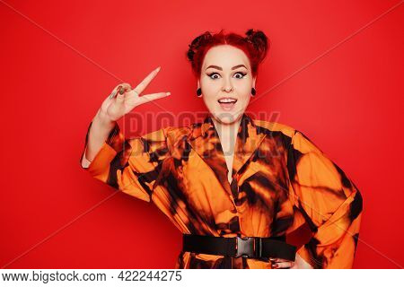 Beautiful Girl On A Red Background. Red Hair And Tunnels In The Ears, Red Dress And Lips. Anime Pose