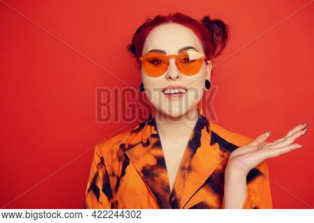 Cute Girl On A Red Background. Red Hair And Tunnels In The Ears, Red Dress And Lips. A Woman In Red