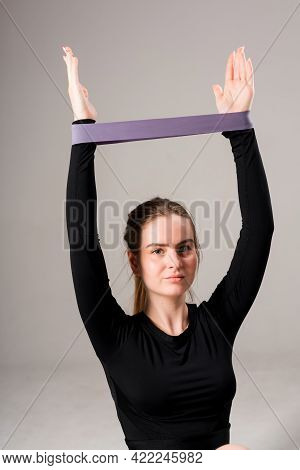 Cute Young Girl Trainer Doing Exercises On The Arms Using An Elastic Band And Raising Her Hands Up