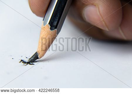 Fingers Holding A Pencil And Nib Broken While Writing On White Paper