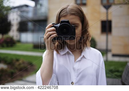 A Beautiful Girl Looks In The Viewfinder In The Camera, And Takes Pictures. The Blonde Learns To Pho