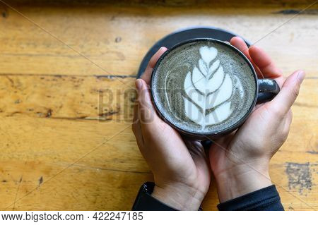 Someone Hands Holding A Cup Of Goth Latte Or Charcoal Latte On Wooden Table (focus On Coffee Surface