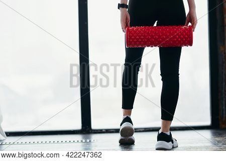 Photo From Behind. Girl Holding Fascia In Her Hands On The Background Of Her Legs In Leggings