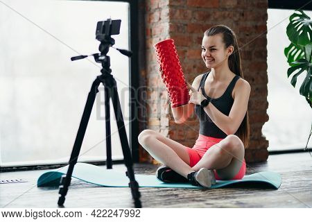 Girl Fitness Trainer Sits On A Yoga Mat And Holds Fascia In Her Hands While Recording Video On A Cam