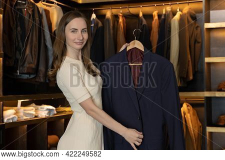 The Saleswoman Smiles And Shows The Clothes In The Costume Shop And Speaks To The Camera