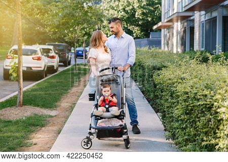 Urban Life With Kids Children. Caucasian Mother And Father Walking With Baby Daughter In Stroller. F
