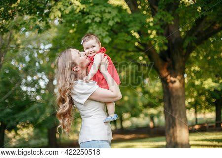 Mothers Day Holiday. Young Smiling Caucasian Mother And Girl Toddler Daughter Hugging In Park. Mom K