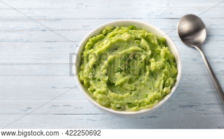 Delicate Mashed Potatoes With Green Peas, Flavored With Butter, Spices And Thyme On A Light Blue Bac