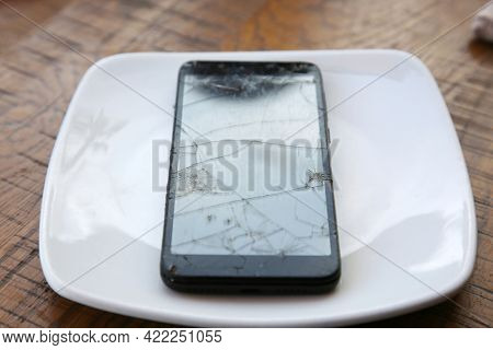 Broken Cellular Telephone. A Cellular Telephone with a cracked and broken Screen on a white plate on a table. Broken Cell Phone.