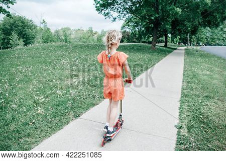 Young Girl Child In Red Orange Romper Riding Scooter On Street Road Park Outdoor. Summer Fun Eco Spo