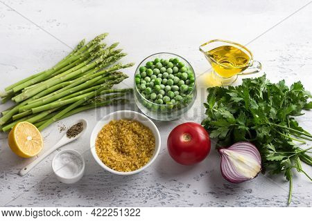 Ingredients For A Middle Eastern Tabbouleh Salad. Bulgur, Fresh Young Green Asparagus, Green Peas, T