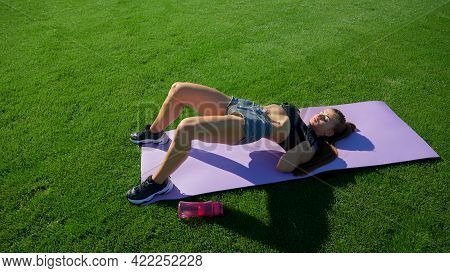 Perfect Muscular Body Of Young Woman Training On Mat On Green Stadium Field. Sexy Fitness Woman Prac