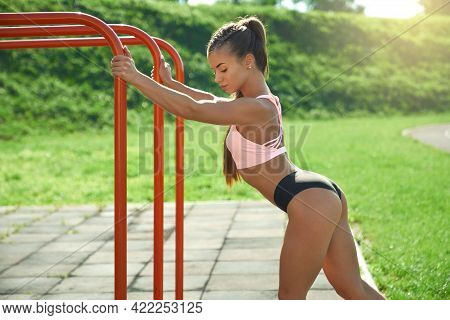Side View Of Stunning Female Runner Posing Near Ladder At Sports Ground In Summer Sunny Day. Young W
