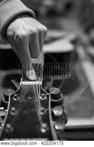 A Service Worker Checks The Sound Of The Guitar For Further Tuning, Black And White Photo.