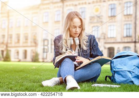 Blond Female Student Is Sitting On Green Grass Yard Near University Campus. Young Woman Is Studying