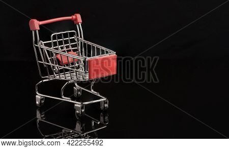 Closeup Red Shopping Trolley Cart With Reflection On Black Background , Commerce And Shopping Concep