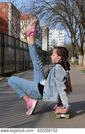 Pretty Girl In Jeans And Pink Sneakers Sits On A Penny Board And Does Exercises. International Skate