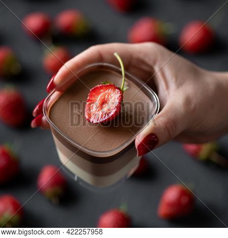 Female Hand Holding Mousse Dessert Decorated With Strawberry In Glass Cup On Black Background. Red B