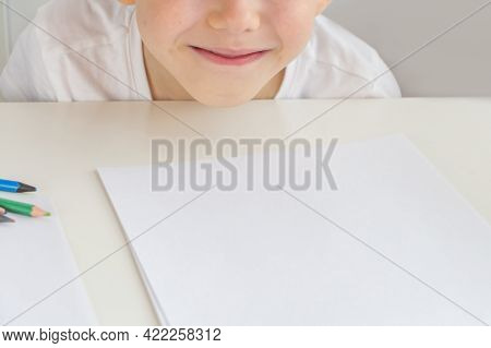 Portrait Of Happy Cute Preschooler Boy 5-6 Years Old At Table With Paper And Pencils. Doing Homework