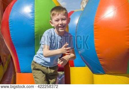 Joyful Child Jumping On Colorful Inflatable Trampoline. Little Boy 5-6 Years Playing On Outdoors Pla