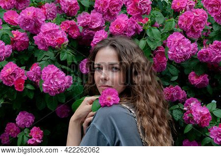 Dreamlike Beautiful Woman With A Rose In Her Hand. She Looks Directly Into The Camera. There Is A Sl