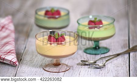Mousse Dessert In Glass With Fresh Raspberries, Mint And Almonds.