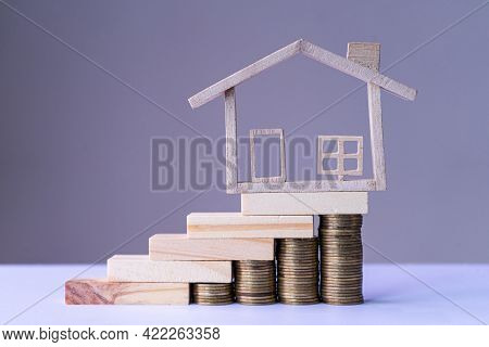 Small Model House On The Stairs Money Coin With White Background. Concept Of Saving To Housing, Loan