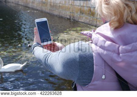 A Girl In A White Cap Photographs The Water Landscape On The Phone. St. Veronicas Day Photographers