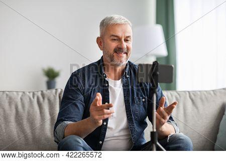 Smiling Senior Man Vlogger Broadcasting From Home
