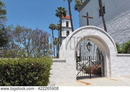 SAN JUAN CAPISTRANO, CALIFORNIA - 27 MAY 2021: Arch, Gate and Cross at the Mission Basilica. The parish church is located just northwest of Mission San Juan Capistrano.