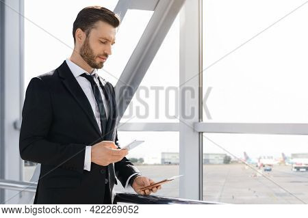 Wealthy Businessman Checking Email While Waiting For Departure, Using Smartphone