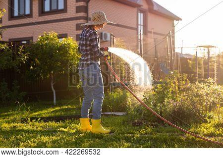 Woman Holding Garden Water Hose Wearing Colorful Wellies Watering Garden