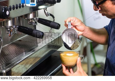 Hand Of Barista Making Latte Or Cappuccino Coffee, Pouring Milk Making Latte Art.