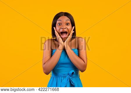 Excited African American Woman In Summer Dress Shouting In Excitement, Holding Hands Near Face, Oran