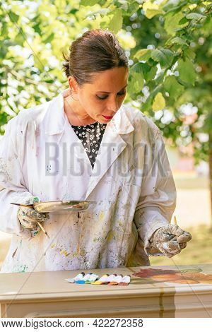 Hispanic Person Painting And Restoring An Old Wooden Furniture. Latin Girl Working With Wood. Carpen