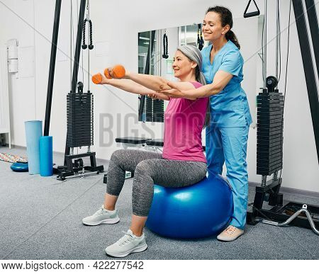Physiotherapist Working With Mature Female Patient In A Rehab Center. Chinese Woman Lifts Dumbbells