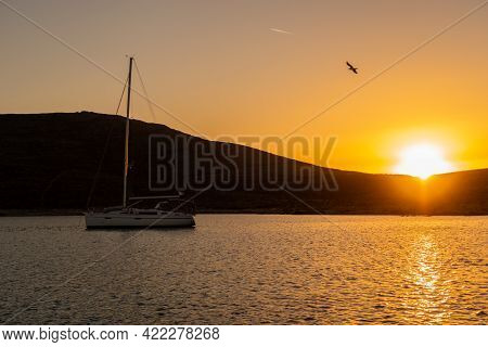 Magical, Vibrant Orange Sunset Over The Hill And Mediterranean Sea With A Silhouette Of A Sailing Bo