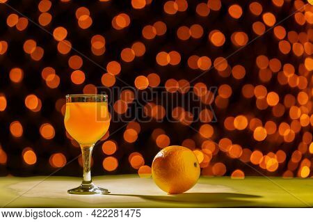 Orange Juice In A Glass Near Oranges On A Black Background Of Blurry Lights. Horizontal Photo